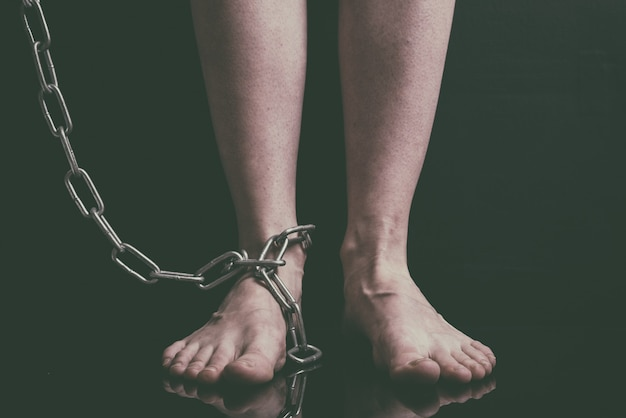 White women feet are on floor chained metal chains close-up