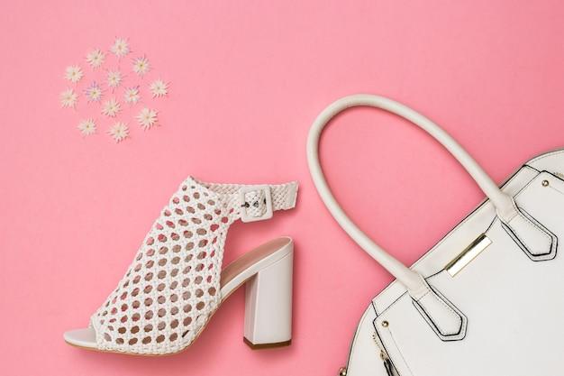 白い女性の靴、白いバッグとピンクの表面の色のパターン
