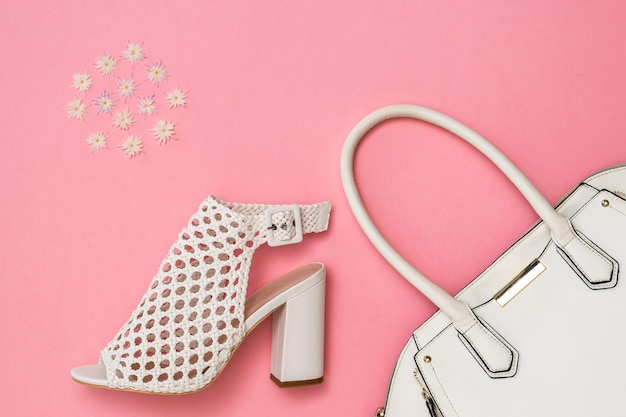White women's shoes, white bag and pattern of color on pink surface