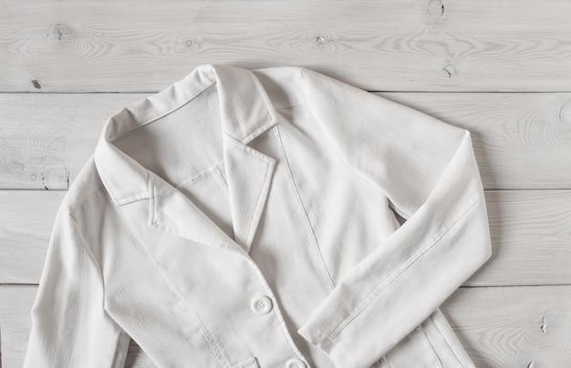 Короткая женская льняная куртка белого цвета. элегантная женская одежда на светлом деревянном фоне.