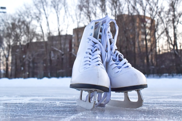 White women's skates stand on the ice. winter entertainment ice rink.