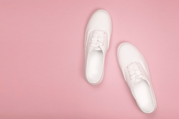 White women's sneakers on a pink background. flat lay, top view and copy space in minimalist style. concept of fashion blog,soft focus