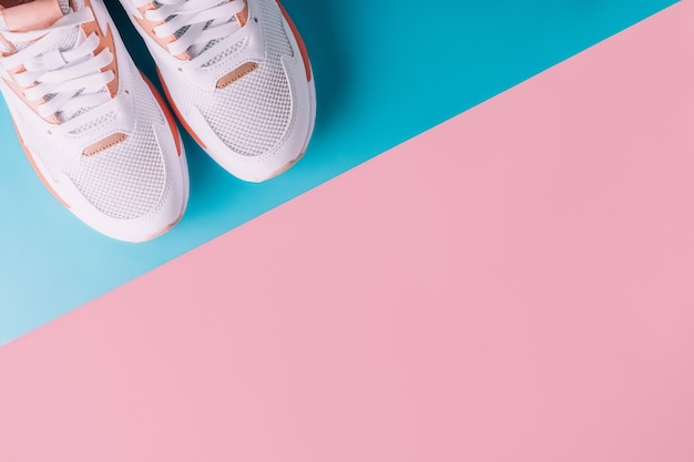 분홍색과 파란색 배경에 산호가 삽입된 흰색 여성용 운동화. 평면도, 평면도. 복사 공간
