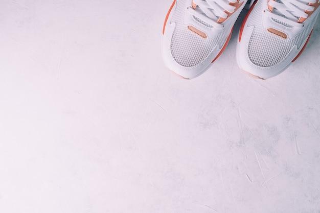 흰색 콘크리트 배경에 산호가 삽입된 흰색 여성용 운동화. 평면도. 평평한 위치, 복사 공간.