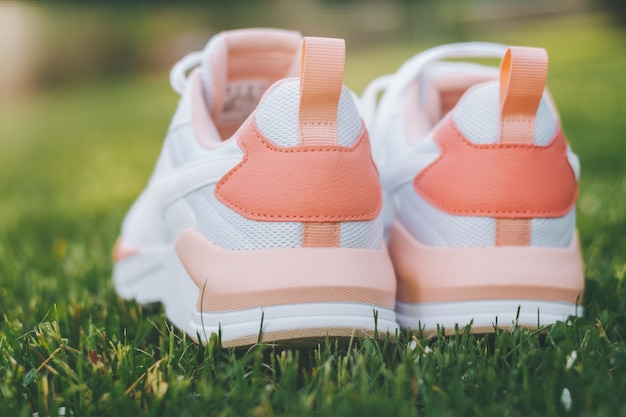 White women's sneakers with coral inserts standing on grass in rays of sunlight. back view