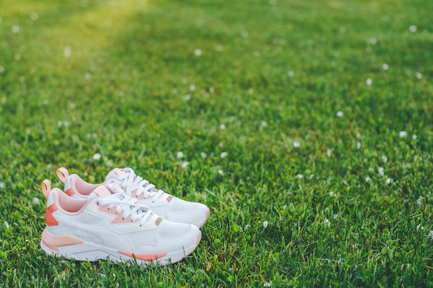 White women's sneakers with coral inserts standing on grass in rays of sunlight. copy space