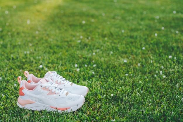 Белые женские кроссовки с коралловыми вставками, стоящие на траве в лучах солнечного света. копировать пространство