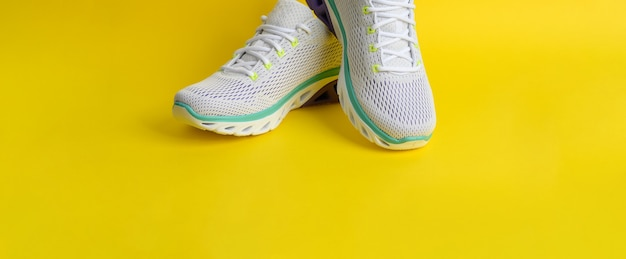 White women's sneakers with laces on a yellow background, banner
