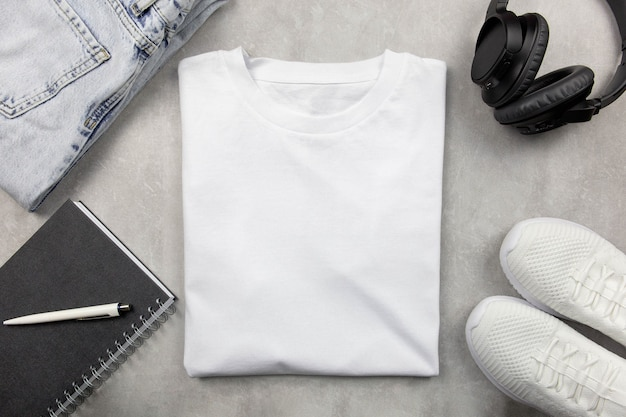 White womens cotton tshirt mockup with jeans and sneakers, notebook and black headphones. design t shirt template, print presentation mock up.