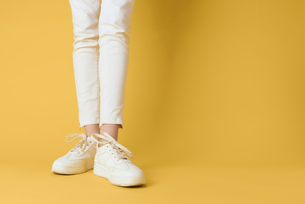 ストリートファッションのトリミングされたビューの孤立した背景をポーズの白い女性のスニーカー