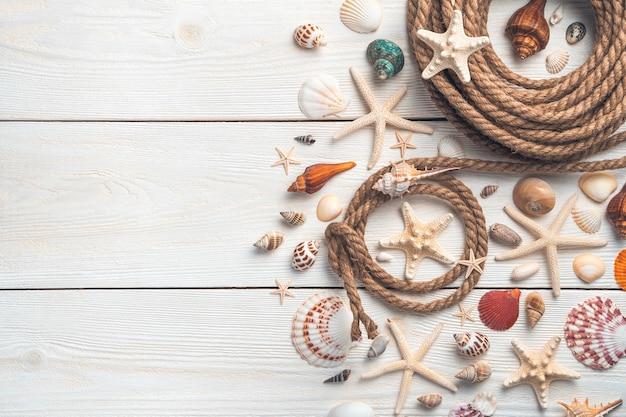 Белый деревянный фон с различными ракушками и морскими звездами и веревками