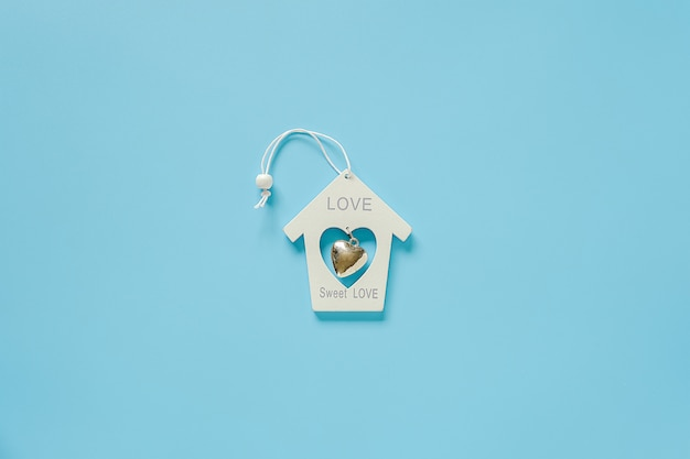 White wood decoration toy house with metal heart on blue background
