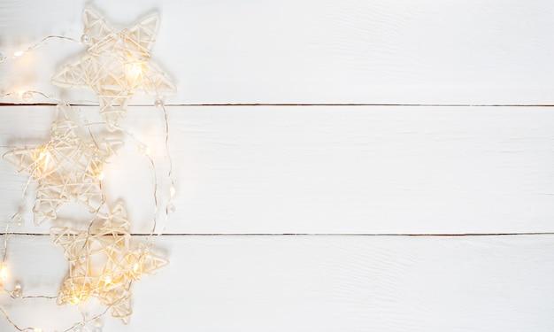 黄色い花輪とコピースペースの星と白い木の水平テクスチャ背景。