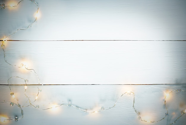 White wood horizontal texture background with yellow garland and copy space with gray vignette.