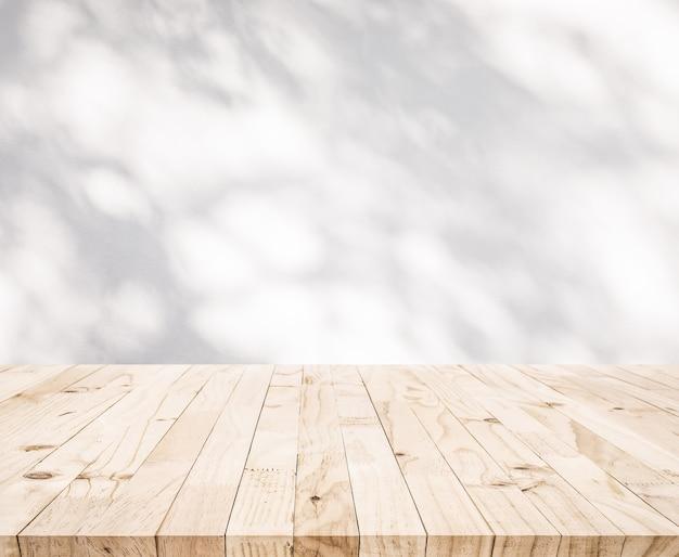 벽 배경에 나무 잎의 그림자와 함께 흰색 나무 테이블 탑. 제품 디스플레이 및 자연 개념