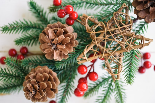 White wood texture with pine leaf, pine cones or conifer cone, red holly balls and wooden star in christmas concept. wood plank background in top view flat lay with copy space for christmas wallpaper.