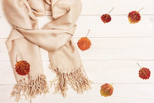 White wood with dry red autumnal season leaves of aspen tree andcozy textile scarf
