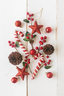White wood with pine cones or conifer cone, red holly balls, glitter star, candy cane and bauble in christmas concept. vertical plank background in top view flat lay copy space for christmas wallpaper