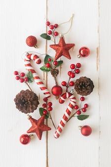 Белая древесина с сосновыми шишками или шишками, красные шарики падуба, звезда с блестками, конфета и безделушка в рождественской концепции. вертикальная планка фон в плоском виде сверху кладут копию пространство для рождественских обоев