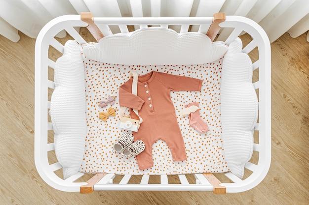 아기 방에 베개 모양의 구름이 있는 흰색 나무 아기 침대. 유아용 침대에 신생아 옷과 액세서리. 어린이 침대의 상위 뷰