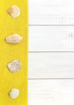 White wooden background, sea shells yellow towels