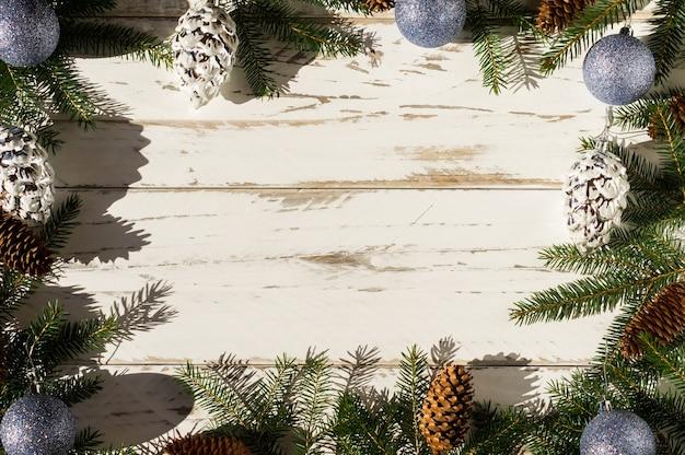 녹색 가문비나무 가지, 천연 원뿔 및 휴일 장난감의 크리스마스 장식이 있는 흰색 나무 배경. 평면도. 공간의 사본.
