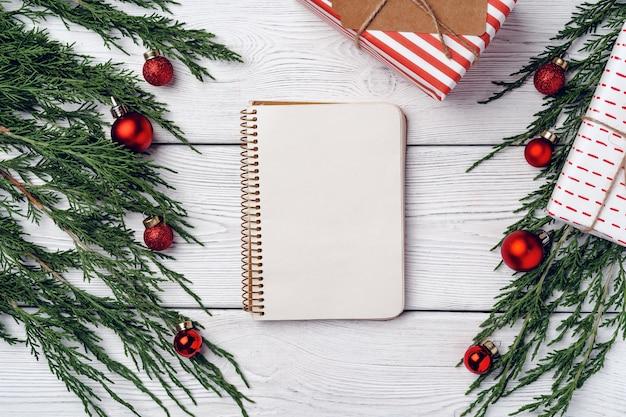 針葉樹の枝とクリスマスの装飾と白い木の背景