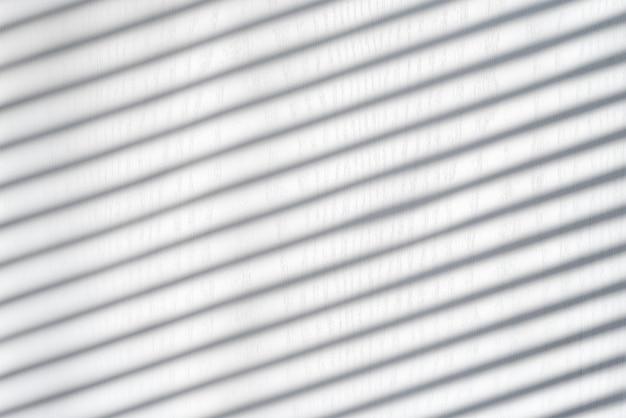 ブラインドからの影と白い木製の背景。晴れた日、インテリア