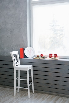 A white wooden bar stool stands near the windowsill and window, on which are christmas red mugs and decor