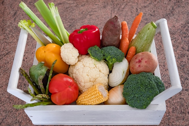 White wooden basket full of different kind of fresh vegetables in white red yellow and green color