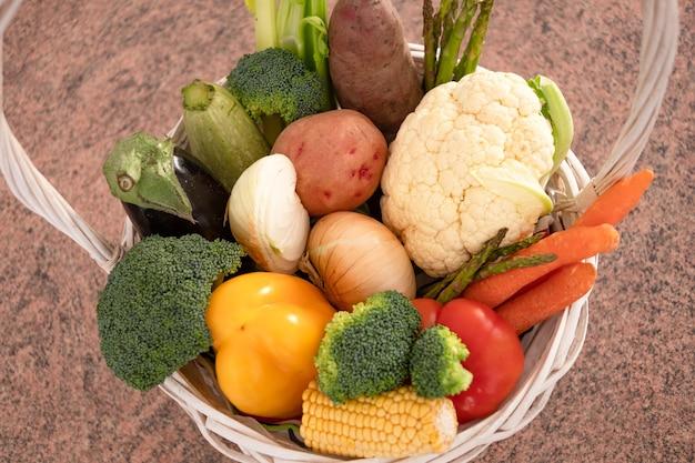 Белая деревянная корзина, полная различных видов свежих овощей белого, красного, желтого и зеленого цвета