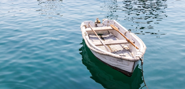 White wooden boat on blue calm water in lake