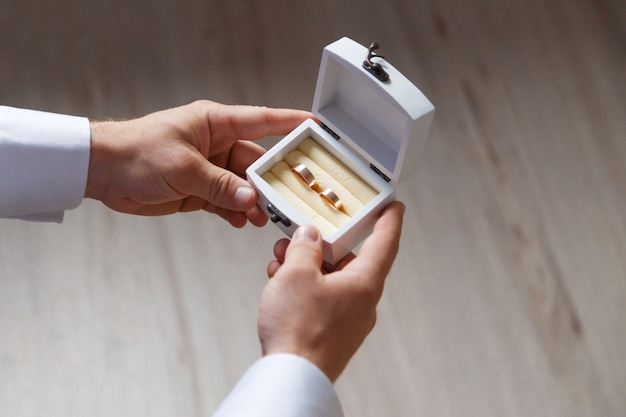 White wooden box with two gold wedding rings in groom hands, close up view, wedding accessories