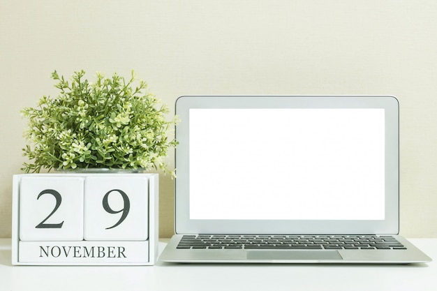 White wooden calendar with black 29 november word with computer notebook