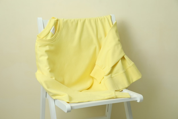 Белый деревянный стул с пустой желтой толстовкой