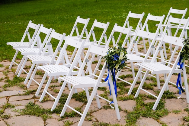 White wooden chairs decorated with flowers and bright satin ribbons, wedding decor at the ceremony.