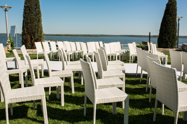 White wooden chairs for guests on a green lawn on outdoor wedding ceremony