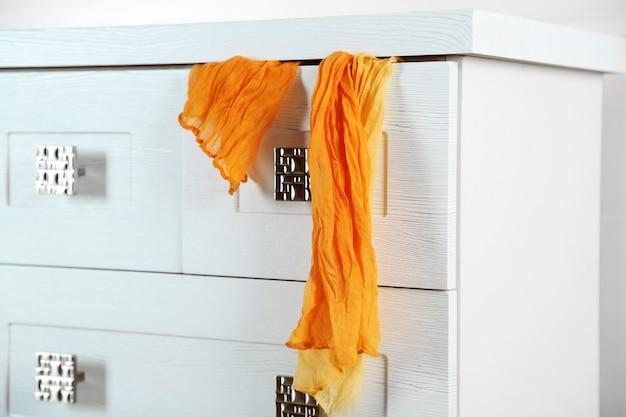 開いた引き出しのスカーフと引き出しの白い木製のたんす