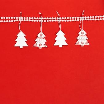 Белая деревянная елка висит на декоре жемчужными бусинами