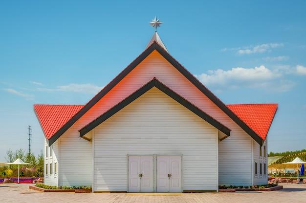 青い空の下の白い木造教会の建物