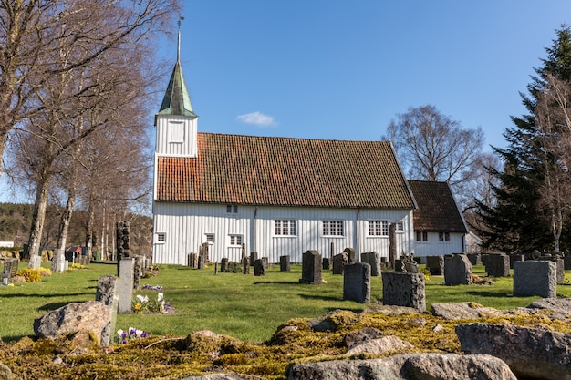 White wooden church in sogne, a parish church in sogne, vest-agder in norway. blue sky, green grass.