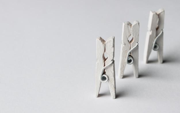 White wooden clothespins on white background.