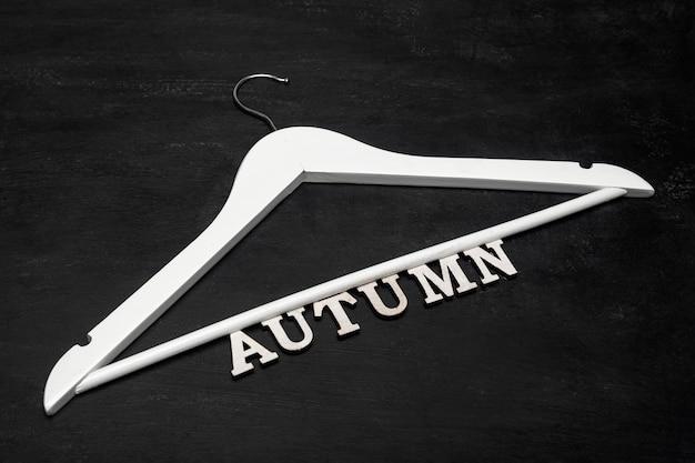 Белая деревянная вешалка для пальто и надпись осень на черном фоне. осенняя концепция коллекции одежды.