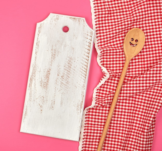 White wooden cutting board and wooden spoon