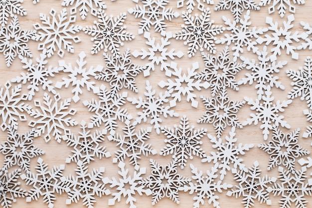 木製の背景、クリスマスの装飾に白い木製の装飾的な雪片。