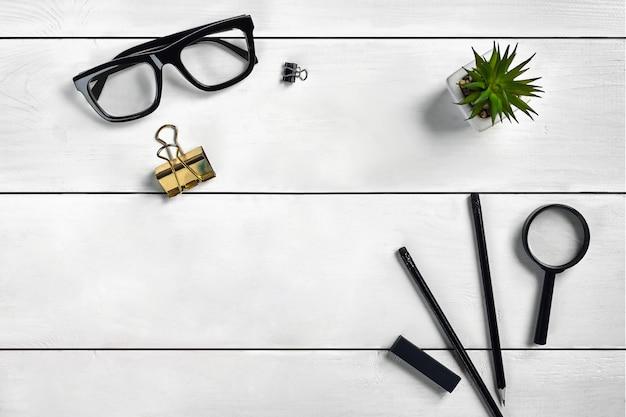 Белый деревянный рабочий стол с очками, двумя карандашами, степлером, лупой и зажимом для папок