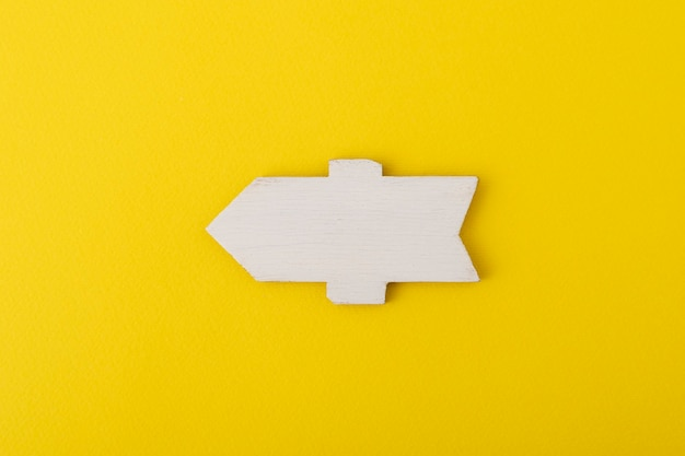 White wooden direction sign on yellow background.