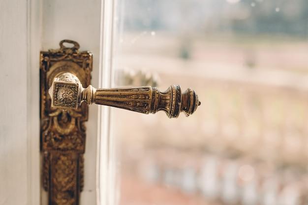 흰색 나무 문과 강철 손 잠금 장치가있는 유리. 창 오래 된 문 손잡이입니다. 텍스트를위한 장소. 빈티지 인테리어.