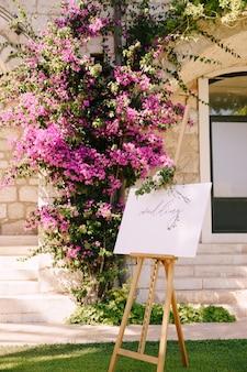 石の壁と咲くバラの茂みの表面に刻まれた白い木製のイーゼル