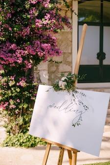 壁の表面に刻まれた白い木製のイーゼルと咲くバラの茂みのタイトル